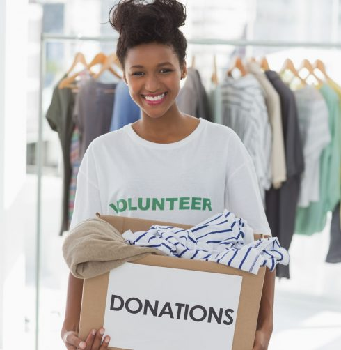 Portrait of a smiling young woman with clothes donation
